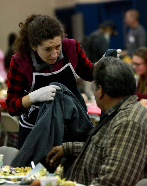 MariaElena Jarson, a member of the Congregation of Emeth, offers a warm coat to a man attending the annual Christmas Day meal at St. Joseph's Family Center in Gilroy, Calif., Sunday, Dec. 25, 2016. The members of the Morgan Hill synagogue have made it an annual tradition to relieve church staff so that they may be with their families on Christmas Day. (Karl Mondon/Bay Area News Group)