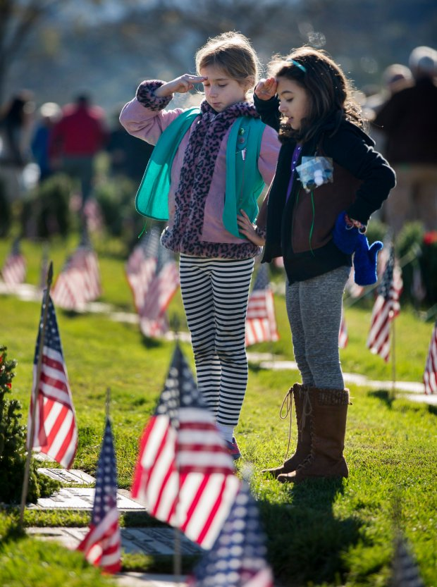 Narya Bower, 9, left, and Paola Rangel, 7, both of Campbell, salute after placing a wreath on a grave as the American Legion Hall #642 of Cupertino participated in the nationwide Wreaths Across America recognition of deceased veterans with a mass wreath-laying event at Gates of Heaven Cemetery in Los Altos, Calif., Saturday, Dec. 17, 2016. Christmas wreaths were laid on graves of deceased service members. (Patrick Tehan/Bay Area News Group)