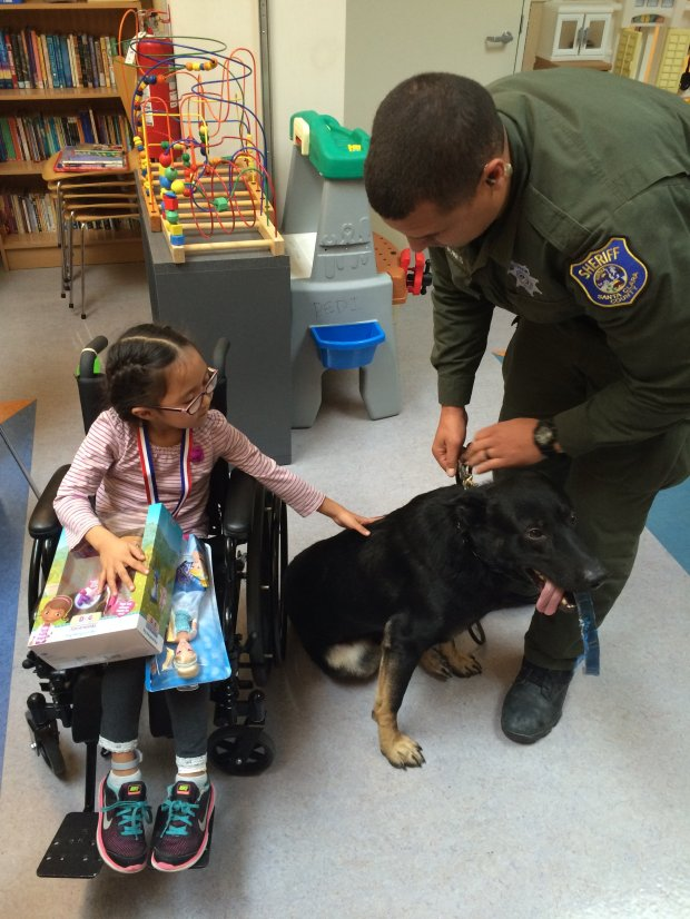 Santa Clara Co. Sheriff's Deputy Jeremy Jones, right, and police K-9 Niner spend time with a pediatrics patient at Valley Medical Center in San Jose as part of a holiday gift giveout on Dec. 8, 2016