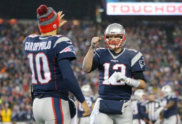 Tom Brady #12 is congratulated by his teammate Jimmy Garoppolo #10 of the New England Patriots after his touchdown against the Pittsburgh Steelers during the third quarter in the AFC Championship Game at Gillette Stadium on January 22, 2017 in Foxboro, Massachusetts. (Photo by Jim Rogash/Getty Images)