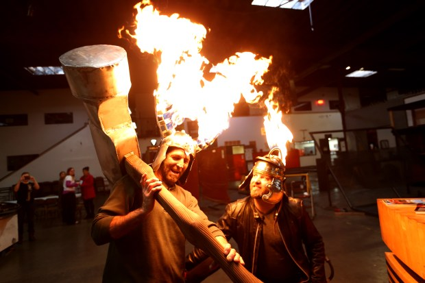 Artists Chris Neimer, left, and Michael Sturtz, founder of The Crucible, are photographed with their polished steel and cooper helmets and a hammer that will be part of the grand finale in the annual Hot Couture fire and fashion show in Oakland, Calif., on Thursday, Jan. 19, 2017. The show runs for four nights from February 16 to 19. (Ray Chavez/Bay Area News Group)