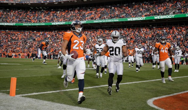 Denver Broncos running back Devontae Booker (23) runs for a touchdown ahead of Oakland Raiders strong safety Nate Allen (20) in the first half of an NFL football game, Sunday, Jan. 1, 2017, in Denver. (AP Photo/Jack Dempsey)