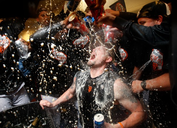 The San Francisco Giants shower San Francisco Giants Aubrey Huff (17) with beer and champagne to celebrate their 3-2 win in Game 6 to win the National League Championship Series at Citizens Bank Park in Philadelphia, Pa on Saturday, October 23, 2010. (Nhat V. Meyer/Mercury News)