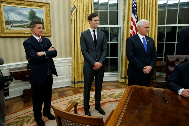 National Security Adviser Michael Flynn, left, Senior Adviser to President Donald Trump Jared Kushner, center, and Vice President Mike Pence watch as Trump signs his first executive order in the Oval Office of the White House, Friday, Jan. 20, 2017, in Washington. (AP Photo/Evan Vucci)