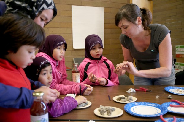 Kristi Holohan, right, community director of the Rock, Paper, Scissors art collective, shows kids how to make jewelry during a jewelry-making class at the Oakland Public library, West Oakland branch, in Oakland, Calif., on Thursday, Feb. 23, 2017. (Ray Chavez/Bay Area News Group)