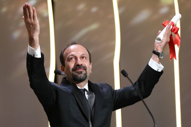 """(FILES) This file photo taken on May 22, 2016 shows Iranian director Asghar Farhadi celebrating on stage after being awarded with the Best Screenplay prize for the film """"The Salesman (Forushande) during the closing ceremony of the 69th Cannes Film Festival in Cannes, southern France. Oscar-winning Iranian director Asghar Farhadi said January 29, 2017y he will not attend next month's Academy Awards, comparing President Donald Trump's visa ban on seven Muslim countries to the actions of hardliners in his own country. Farhadi, nominated for Best Foreign Language Film for """"The Salesman"""", said in a statement carried by Iranian news agencies that he had initially planned to attend the ceremony in Los Angeles, but had been forced to change his mind. / AFP PHOTO / Valery HACHEVALERY HACHE/AFP/Getty Images"""
