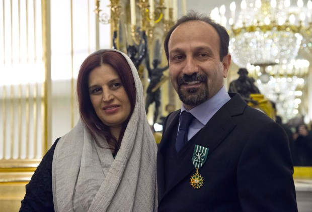 """FILE -- In this Feb. 27, 2014 file photo, Iranian film director Asghar Farhadi, right, and his wife Parisa, pose after he was awarded the Officer of the Order of Arts and Letters medal, at the French Ministry of Culture, in Paris, France. The Oscar-nominated Iranian director says he will not attend this year's Academy Awards because of a travel ban imposed by President Donald Trump. Farhadi, whose film, """"The Salesman,"""" was nominated for best foreign film, says the uncertainty surrounding his ability to travel to the United States was """"in no way acceptable,"""" and that he would not attend the ceremony even if an exception to the ban were possible. (AP Photo/Michel Euler, File)"""