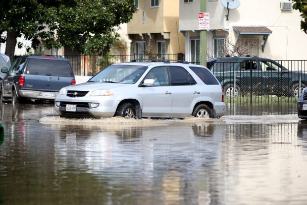A resident drives his vehicle along a flooded Rock Springs Drive in San Jose, Calif., on Wednesday, Feb. 22, 2017. (Anda Chu/Bay Area News Group)