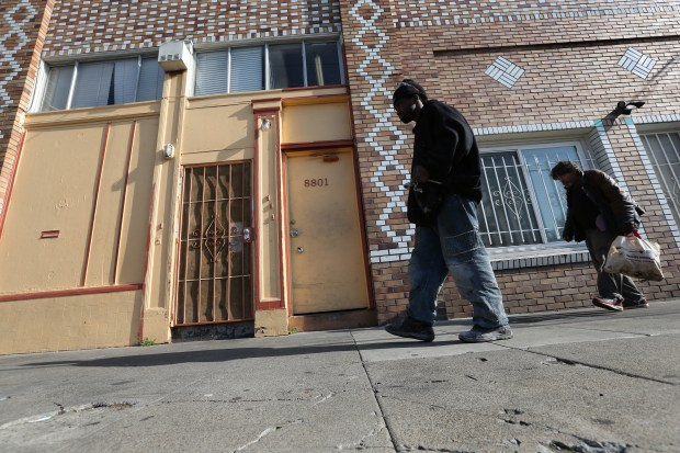 Pedestrians walk past the building at 8801 International Boulevard in Oakland, Calif., which is listed as transitional housing by Urojas Community Services on Thursday, March 30, 2017. The property has a number of code enforcement complaints over the last decade. (Ray Chavez/Bay Area News Group)