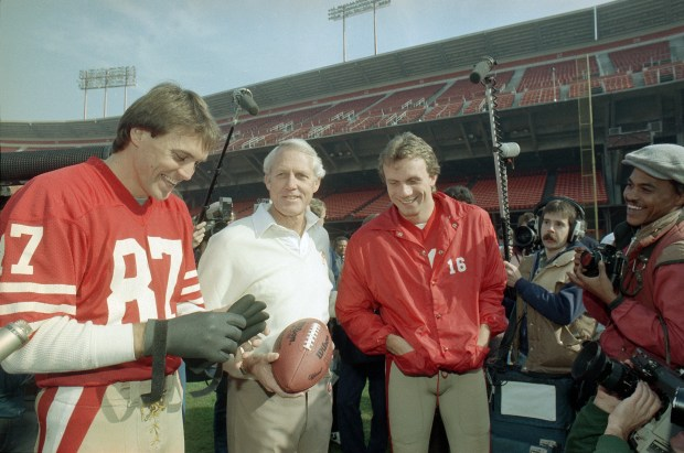 San Francisco 49ers' head coach Bill Walsh, center, shares a laugh with quarterback Joe Montana, in red jacket at right, and receiver Dwight Clark, left, during picture day at San Francisco's Candlestick Park, Jan. 16, 1985. The 49ers will meet the Miami Dolphins in Super Bowl XIX on Sunday. (AP Photo)