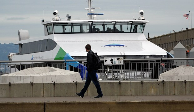 A pedestrian eyes SF Bay Ferry's new $15 million addition to their fleet , the Hydrus, docked at Pier 9 in San Francisco, Calif., Monday, March 20, 2017. The 400-seat ferry, able to accommodate 50 bicycles, will begin service this week between the East Bay and San Francisco. (Karl Mondon/Bay Area News Group)