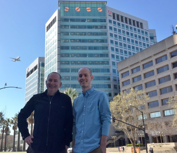New York artist Ben Rubin and Tennessee high school teacher Jimmy Waterspose in front of the Adobe headquarters building with Rubin's San Jose Semaphore project that Waters solved. (Sal Pizarro/Staff)