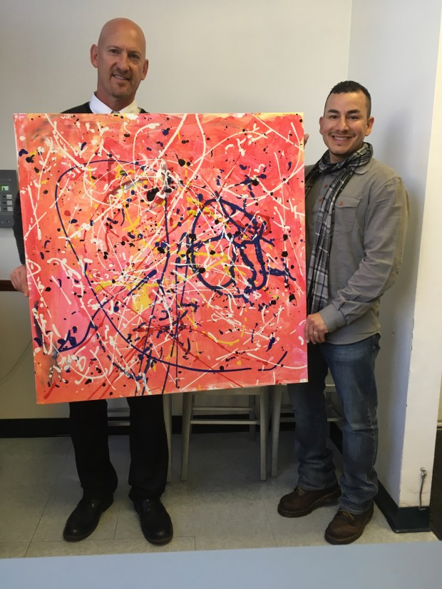 Selby Lane School Principal Warren Sedar, left, and Cesar Zuniga with a Jackson Pollock-inspired drip painting made by all 1st graders at Selby and 7th grade Menlo School students. (Courtesy photo)