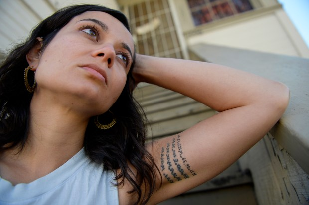 Carmen Brito, 29, of Oakland, sits on the front porch of her home in Oakland, Calif. on Saturday, April 29, 2017. Brito is a survivor of the Ghost Ship warehouse fire. She rented a room on the first floor and was sleeping when the fire broke out late that evening on December 2, 2016. On her left arm Brito has tattooed coordinates of important places in her life. The first coordinate is the house she grew up in, the second is the university she attended, the third is her home in Bangkok, Thailand and the last one is the Ghost Ship warehouse. (Jose Carlos Fajardo/Bay Area News Group)