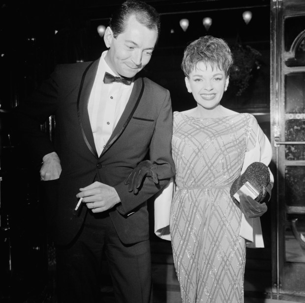 American actress and singer Judy Garland (1922 - 1969) and her partner Mark Herron (1928 - 1996) attend the 'Night of 100 Stars' at the London Palladium, 23rd July 1964. (Photo by Terry Disney/Express/Getty Images)