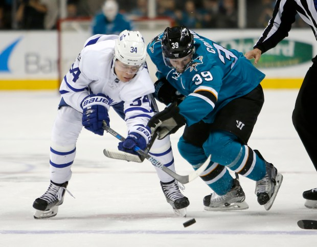 Toronto Maple Leafs' Auston Matthews (34) fights for the puck against the San Jose Sharks' Logan Couture (39) in the first period of their NHL game at SAP Center in San Jose, Calif., on Tuesday, Feb.28, 2017.(Josie Lepe/Bay Area News Group)