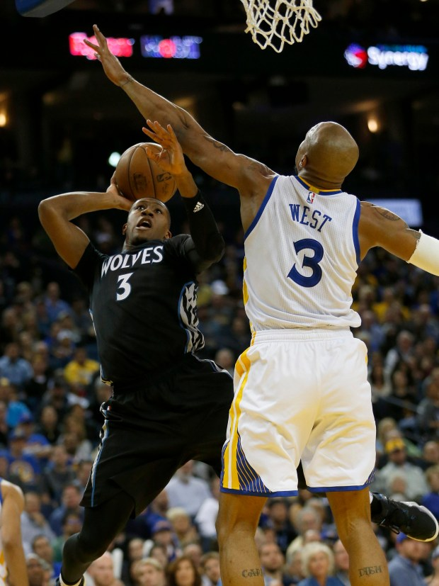 Minnesota Timberwolves' Kris Dunn (3) shoots over Golden State Warriors' David West (3) in the fourth quarter of their NBA game at Oracle Arena in Oakland, Calif., on Tuesday, April 4, 2017. (Jane Tyska/Bay Area News Group)