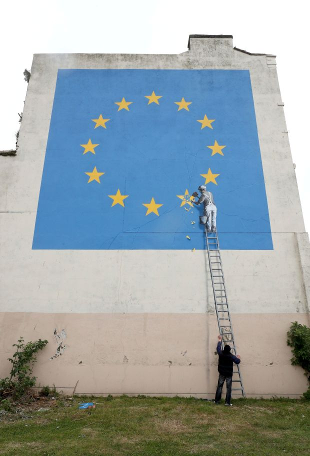A man has a picture taken next to a mural by artist Banksy of a workman removing a star from the EU flag in Dover England on Monday May 8, 2017. (Gareth Fuller/via AP)