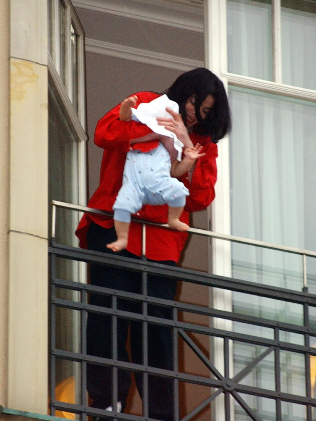 Singer Michael Jackson holds his son eight-month-old son Prince Michael II over the balcony of the Adlon Hotel November 19, 2002 in Berlin, Germany. Jackson is in Berlin with his three children to accept a lifetime achievement award. (Photo by Olaf Selchow/Getty Images)
