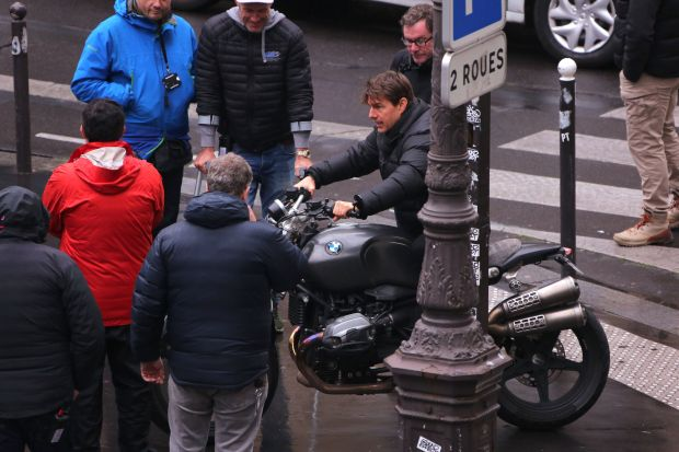 "US actor Tom Cruise (R) sits on a motorcycle during the filming of ""Mission Impossible 6"" in a Paris street on May 3, 2017. / AFP PHOTO / STRINGERSTRINGER/AFP/Getty Images"