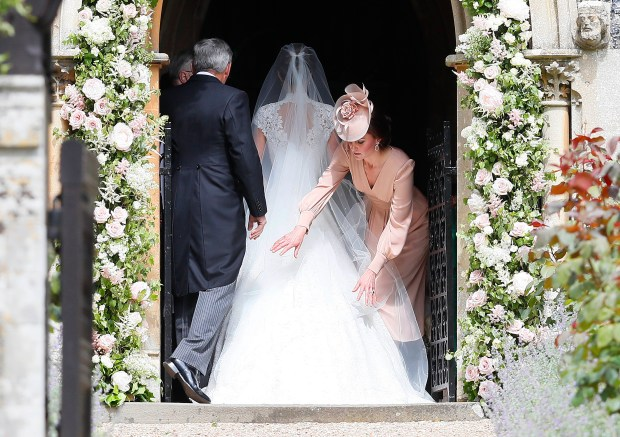 ENGLEFIELD, ENGLAND - MAY 20: Catherine, Duchess of Cambridge, right, arranges the train of her sister of her sister Pippa Middleton as she arrives with her father Michael Middleton for her wedding to James Matthews at St Mark's Churchon May 20, 2017 in Englefield, England. Middleton, the sister of Catherine, Duchess of Cambridge is to marry hedge fund manager James Matthews in a ceremony Saturday where her niece and nephew Prince George and Princess Charlotte are in the wedding party, along with sister Kate and princes Harry and William. (Photo by Kirsty Wigglesworth - Pool/Getty Images)