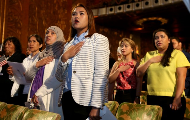 Citizenship applicants stand during the singing of the National Anthem at a naturalization ceremony at the Paramount Theater in Oakland, Calif., on Thursday, May 4, 2017. More than 1,000 people from 89 countries of origin became United States Citizens at the ceremony. (Anda Chu/Bay Area News Group)