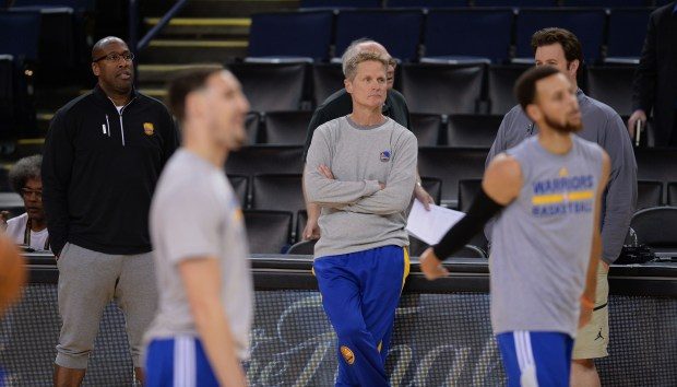 The Golden State Warriors coaches Steve Kerr and Mike Brown watch at a workout during media day for the NBA Finals at Oracle Arena in Oakland, Calif., on Wednesday, May 31, 2017. The NBA Finals between the Golden State Warriors and the Cleveland Cavaliers begins tomorrow. (Dan Honda/Bay Area News Group)