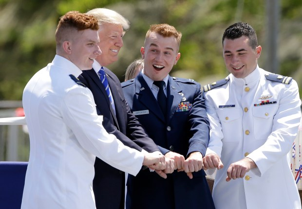 President Donald Trump poses for a photo with U.S. Coast Guard Academy graduate Ryan Carpenter, left, and his brothers, U.S. Air Force Capt. Kory Carpenter, center right, and U.S. Coast Guard Lt. Junior Grade Kyle Carpenter, right, during commencement exercises at the U.S. Coast Guard Academy, Wednesday, May 17, 2017, in New London, Conn. (AP Photo/Steven Senne)