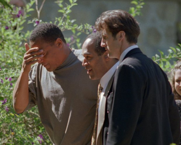 O.J. Simpson, center, walks into his home in the Brentwood section of Los Angeles, Calif., with his friend, Al Cowlings, left and an unidentified man after he was acquitted of the double-murder of his ex-wife Nicole Brown and Ronald Goldman in Los Angeles Tuesday, Oct. 3, 1995.(AP Photo/Reed Saxon)