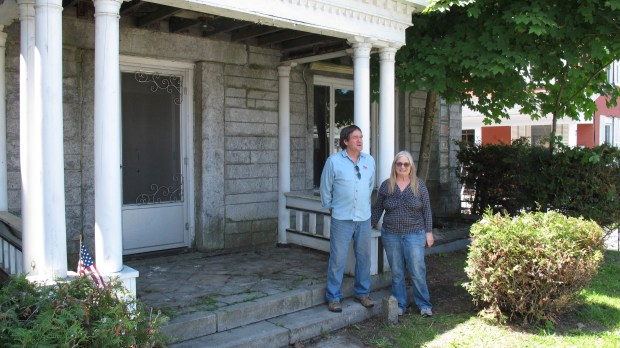Brian and Joan Dumoulin pose on both sides of a marker showing the U.S.-Canadian border in the front yard of their home. She is in Canada, while he is in the United States. (AP Photo/Wilson Ring)
