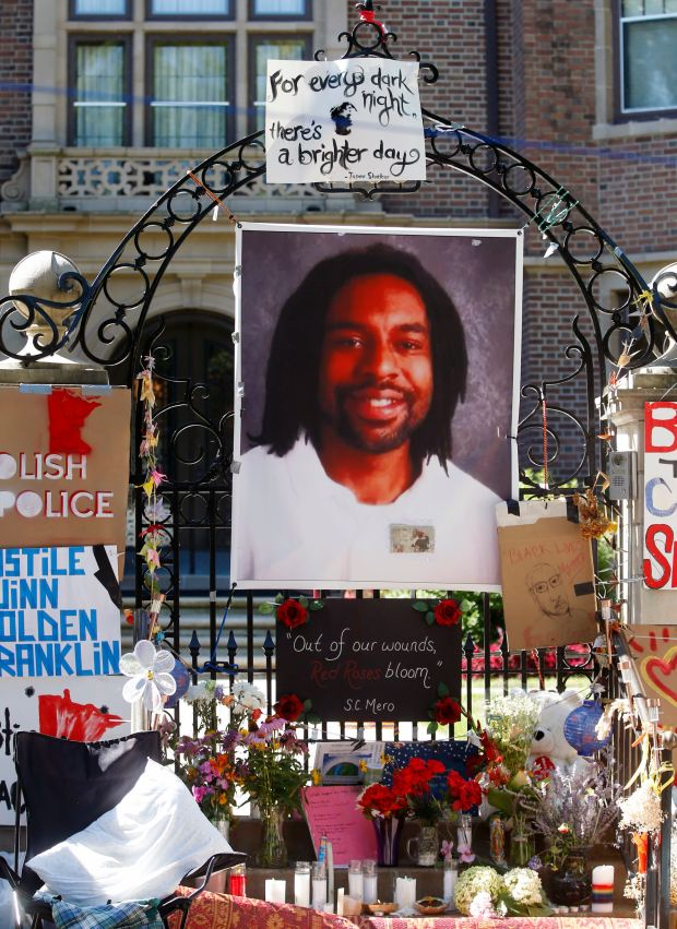 A memorial including a photo of Philando Castile adorns the gate to the governor's residence in St. Paul, Minn., July 2016. (AP Photo/Jim Mone, File)