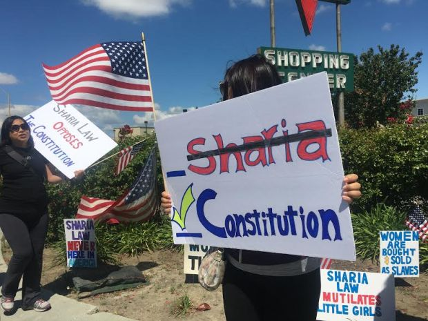 A woman holds a sign opposing Sharia law in a protest in Santa Clara on Saturday June 10