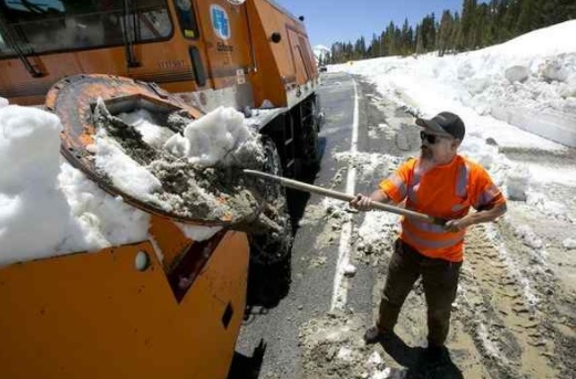 In this photo taken June 6, Caltrans maintenance worker Paul Jensen removes snow and dirt that is clogging the rotary blower he is operating to clear snow from Highway 120 near near Yosemite National Park, Calif. This year's heavy snowfall has crews working to clear Highway 120 as summer approaches; the only road through Yosemite that connects the Central Valley on the west side with the Owens Valley on the east side of the Sierra Nevada. (RICH PEDRONCELLI — THE ASSOCIATED PRESS)