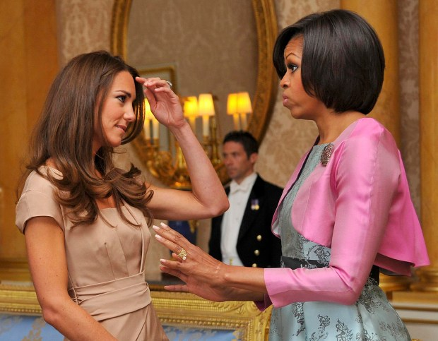 """Britain's Catherine, Duchess of Cambridge (L) speaks with US First Lady Michelle Obama at Buckingham Palace, in central London, on May 24, 2011. US President Barack Obama Tuesday basked in the lavish royal pageantry of a state visit to Britain, given an extra dash of glamour by a brief encounter with Prince William and his bride Catherine. But the 24-hour demands that follow a US president everywhere shadowed the London pomp, as Obama took time out to say he was """"heartbroken"""" at the toll of vicious tornados which ripped across the US midwest, killing 116 people. AFP PHOTO / TOBY MELVILLE/POOL (Photo credit should read TOBY MELVILLE/AFP/Getty Images)"""