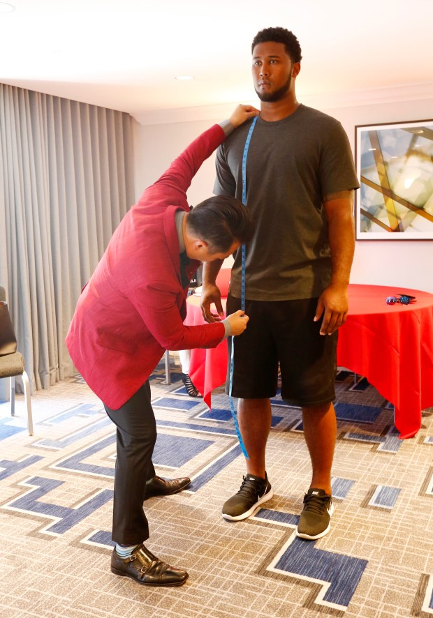 Defensive lineman, DeForest Buckner, of the 49ers, right, is measured by designer, Andrew Jang, left, for a tailored suit during a fitting session at the Marriott Hotel in Santa Clara, California, on Wednesday, July 26, 2017. (Gary Reyes/ Bay Area News Group)