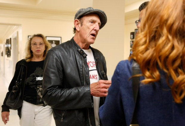 """Michael Zegaris, Oakland Athletics team photographer, center, talks to Tabitha Soren, former MTV VJ and now photographer, during the opening reception of her exhibition called """"Fantasy Life"""" at San Francisco City Hall in San Francisco, Calif. on Thursday, July 20, 2017. (Nhat V. Meyer/Bay Area News Group)"""