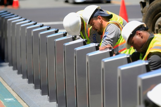 An installation team works on securing the bike racks for Ford GoBike outside City Hall in Emeryville, Calif., on Thursday, July 6, 2017. Ford GoBike, formerly known as Bay Area Bike Share, is in the process of installing stations throughout the East Bay as part of its ten-fold expansion from 700 bikes to 7,000. (Laura A. Oda/Bay Area News Group)