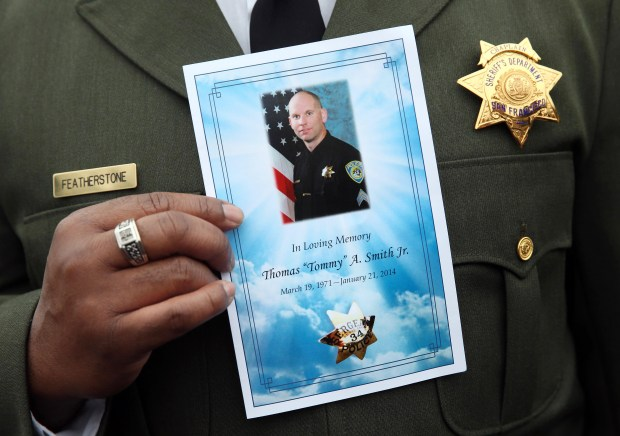 Chaplain Donnie Featherstone, of the San Francisco Sheriff's Department, holds a program during the funeral of BART police Sgt. Thomas Smith Jr.at the Neighborhood Church in Castro Valley, Calif., on Wednesday, Jan. 29, 2014. His brothers Deputy Edward Smith of the Alameda County Sheriff's Office, Patrick Smith, of the Newark police department, and brother-in-law and K-9 Officer Todd Shaheen, of the Hayward police department, were pallbearers. (Jane Tyska/Bay Area News Group)