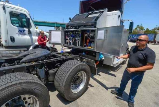 TransPower's Frank Falcone, left, and Matt Vito open the covers on the back of a hydrogen fuel-cell electric truck at the Total Transportation Services Inc. office in Long Beach on Wednesday, July 26, 2017. The ports of LA and LB just vowed to spend $14 billion to clean the air, largely with zero and near-zero-emissions-producing big-rig trucks. (Scott Varley — Staff photographer)