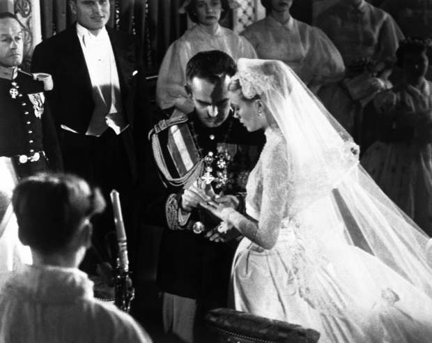 Prince Rainier places the ring on Grace Kelly's finger during their wedding in Monaco Cathedral on April 19, 1956. (AP Photo)