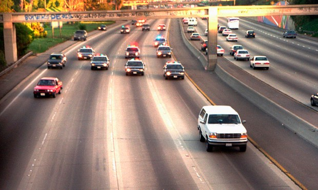 FILE - In this June 17, 1994 file photo, a white Ford Bronco, driven by Al Cowlings carrying O.J. Simpson, is trailed by Los Angeles police cars as it travels on a freeway in Los Angeles. Simpson's ex-wife, Nicole Brown Simpson, and her friend Ronald Goldman are found dead in Los Angeles. Simpson is later arrested after a widely televised freeway chase in his white Ford Bronco. (AP Photo/Joseph Villarin, File)