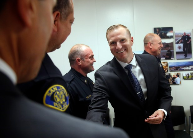 Kyle Burchfiel, left, is greeted by members of the San Jose Police Department, as he returns for his second stint as an officer Monday, July 31, 2017, in San Jose, California. Burchfiel, formerly with the Palo Alto Police Department, is among a growing number of returning SJPD veterans. (Karl Mondon/Bay Area News Group)
