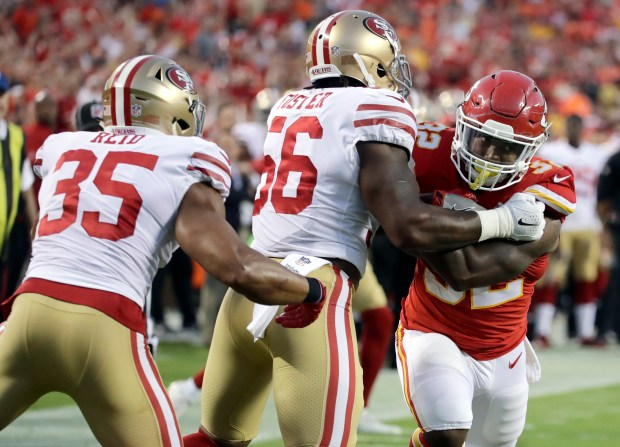 Reuben Foster (56) and Eric Reid (35) tackles Kansas City Chiefs running back Spencer Ware during the first half of Friday's exhibition opener won by the 49ers in Kansas City. (AP Photo/Charlie Riedel)