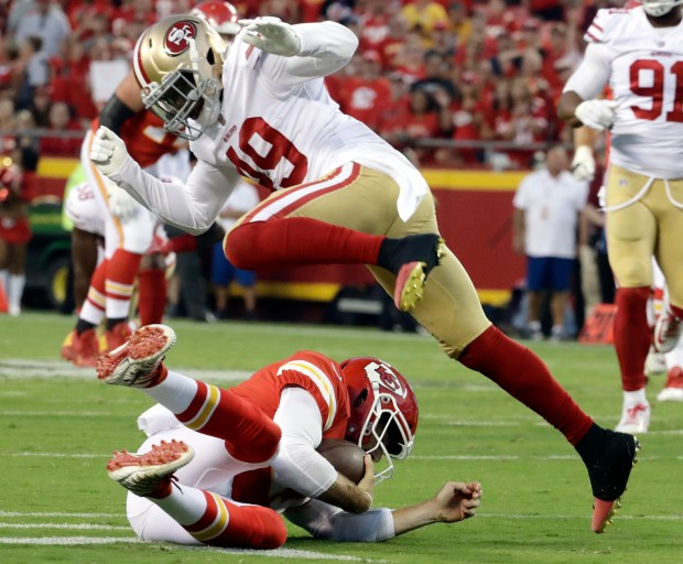 San Francisco 49ers defensive back Lorenzo Jerome (49) leaps over a sliding Kansas City Chiefs quarterback Alex Smith (11) during the first half of an NFL preseason football game in Kansas City, Mo., Friday, Aug. 11, 2017. (AP Photo/Charlie Riedel)