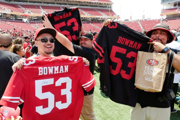 Mike Bongato, 42, of San Francisco, at left, Ricardo Lopez, 34, of San Jose, and Andrew Moreno, 23, of Salinas, show off their signed Navarro Bowman jerseys after San Francisco 49ers practice at Levi's Stadium on Saturday, Aug. 5, 2017, in Santa Clara, Calif. (Jim Gensheimer/Bay Area News Group)