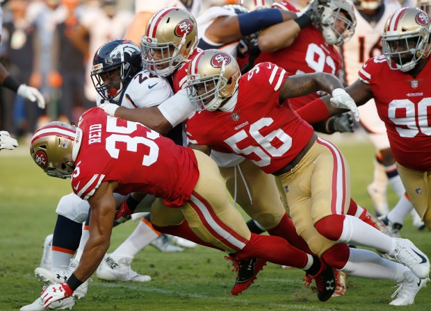 Denver Broncos running back C.J. Anderson (22) is tackled by San Francisco 49ers defensive end Arik Armstead (91) with help from free safety Eric Reid (35), and linebacker Reuben Foster (56) in the first quarter at Levi's Stadium on Saturday, Aug. 19, 2017, in Santa Clara, Calif. (Jim Gensheimer/Bay Area News Group)