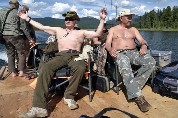 TOPSHOT - Russian President Vladimir Putin (L), accompanied by defence minister Sergei Shoigu, gestures as he fishes in the remote Tuva region in southern Siberia. The picture taken between August 1 and 3, 2017. / AFP PHOTO / SPUTNIK / Alexey NIKOLSKY (Photo credit should read ALEXEY NIKOLSKY/AFP/Getty Images)