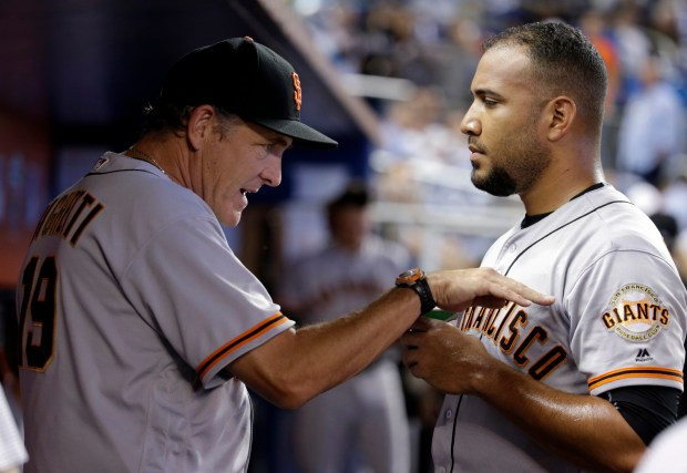 San Francisco Giants pitching coach Dave Righetti (19) talks with relief pitcher Albert Suarez during the fifth inning of a baseball game against the Miami Marlins, Wednesday, Aug. 16, 2017, in Miami. The Marlins won 8-1. (AP Photo/Lynne Sladky)