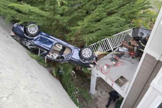 A firefighter checks on the BMW 528i that sits upside down wedged between a retaining wall and the deck of a house in Paradise Cay after the driver lost control on Paradise Drive and plummeted 80 feet, bouncing off the house in Tiburon on Wednesday. (James Cacciatore/Special to the Marin Independent Journal)