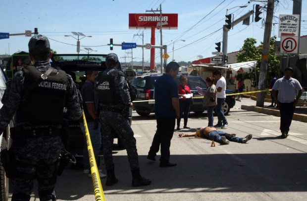 Federal police tape off the area where a man who was shot dead in broad daylight on a central avenue in Acapulco, Mexico, Sunday, Aug. 13, 2017. (AP Photo/Bernandino Hernandez)